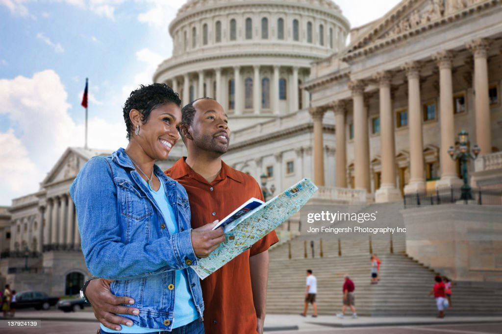 Black couple sightseeing with map : Stock Photo