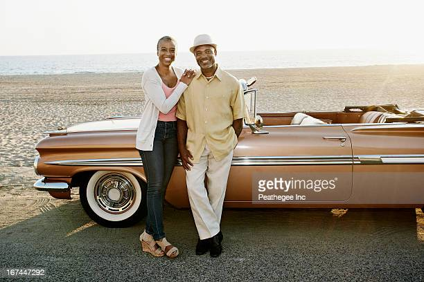 Black couple standing by convertible