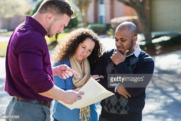 Noir couple debout sur la rue résidentielle avec agent