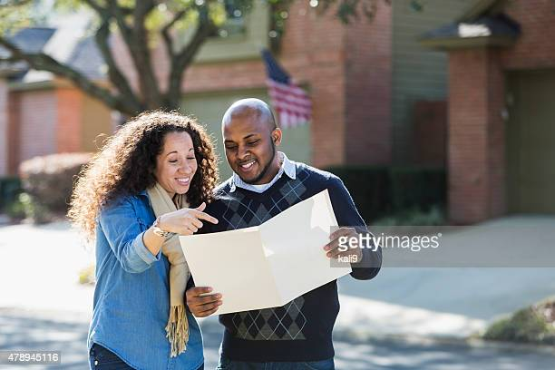Black couple standing outdoors on residential street