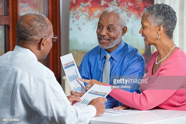 Black couple talking to businessman