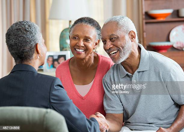 Black couple talking to businesswoman