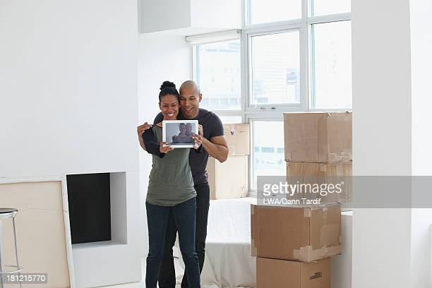 Black couple using tablet computer in new house