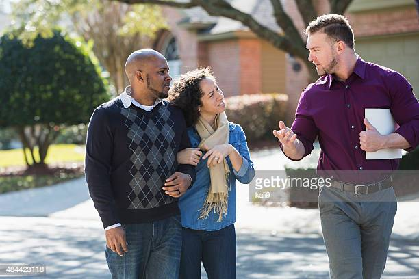 Noir couple marchant sur la rue résidentielle avec agent