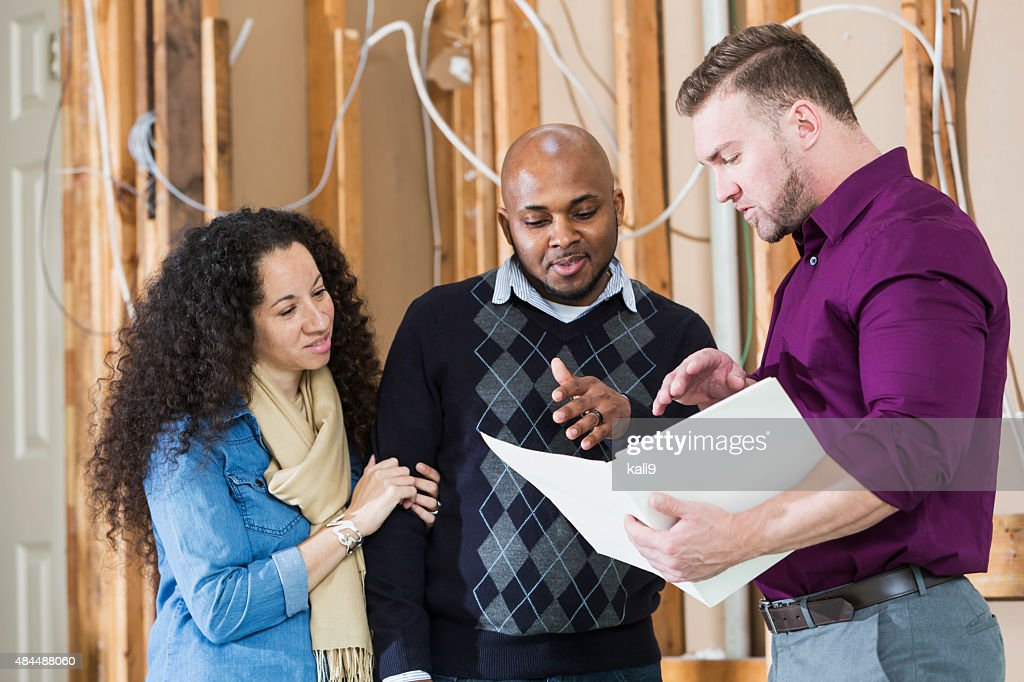 Black couple with contractor remodeling home : Stock Photo