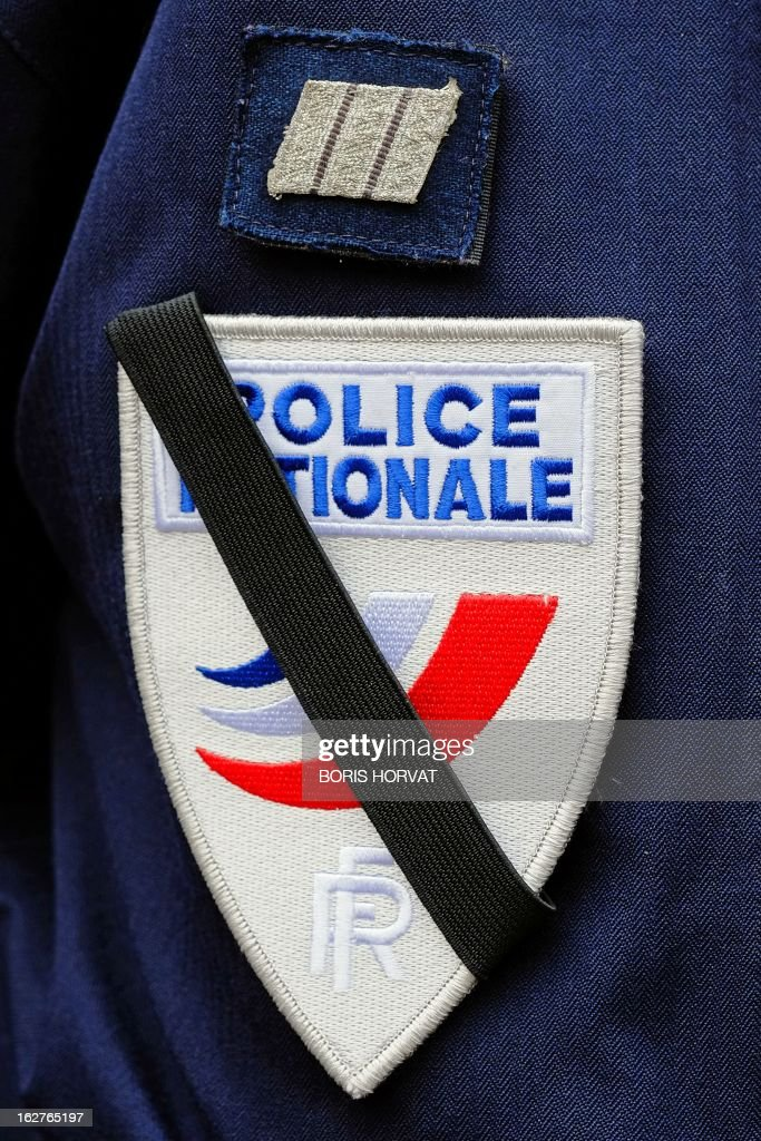 A black crepe is seen on the shield of a policeman during an homage, on February 26, 2013, in Marseille, southern France, to his two colleagues killed in a collision in Paris during a high-speed chase, five days ago. An alleged drunk driver killed the two Paris police officers after slamming his black Land Rover into their cruiser during a high-speed chase on the ring road around Paris. HORVAT