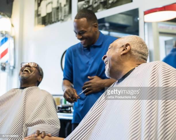 Black customers and barber laughing in retro barbershop