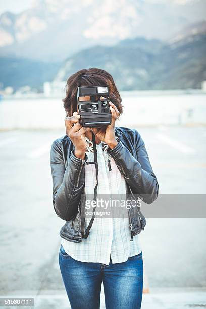 Black cute woman photographing with istant camera