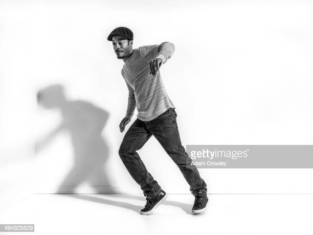 Black dancer casting shadow on wall