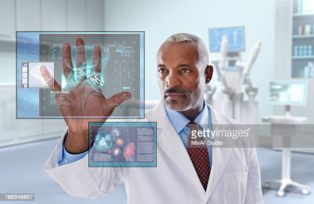 Black doctor looking at digital display in doctor's office