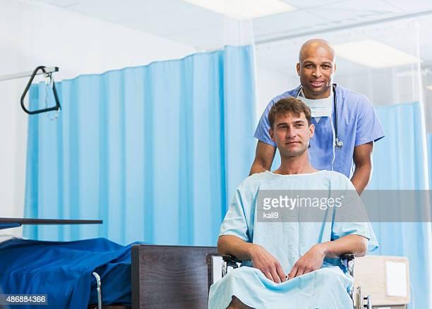 Negro médico o enfermera con el paciente para silla de ruedas