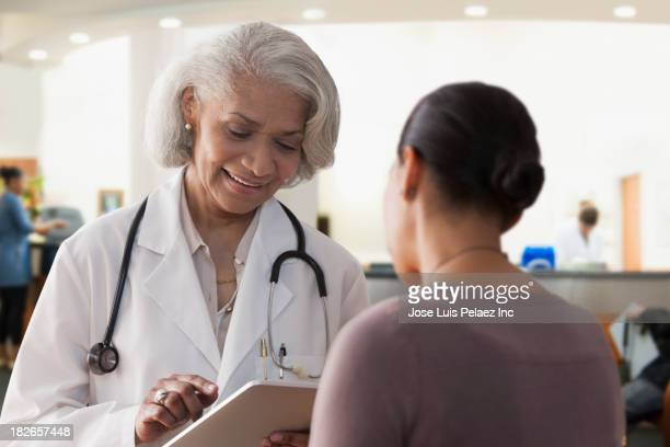 Black doctor talking to client in hospital