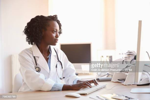 Black doctor typing on computer