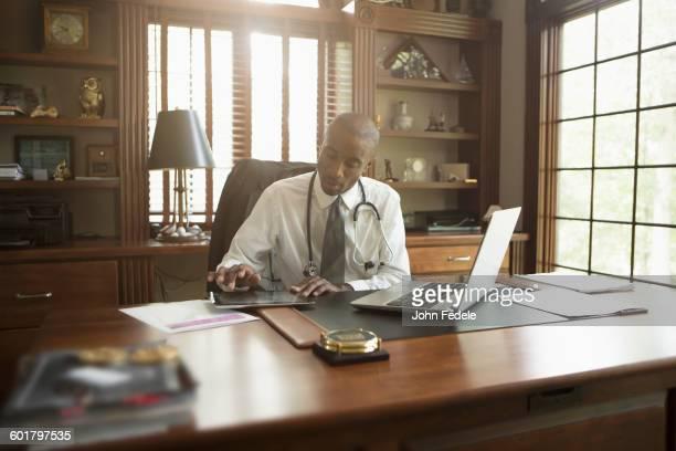 Black doctor using digital tablet in office