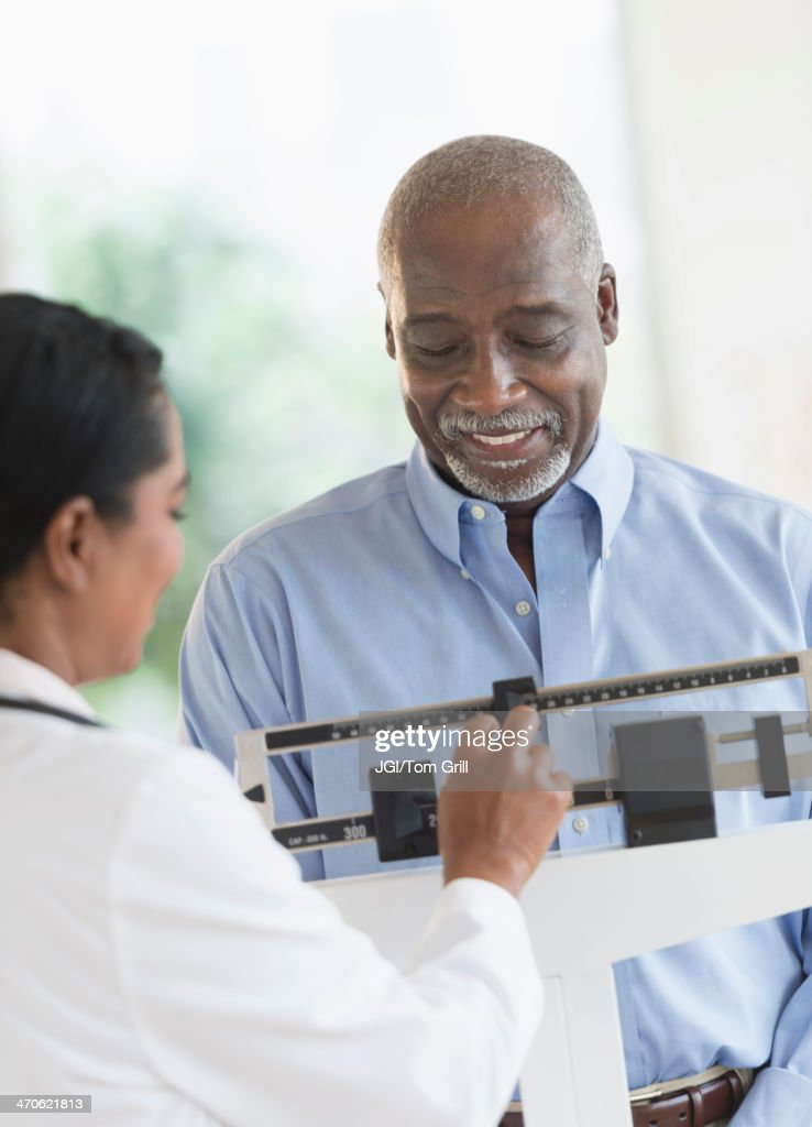 Black doctor weighing patient : Stock Photo