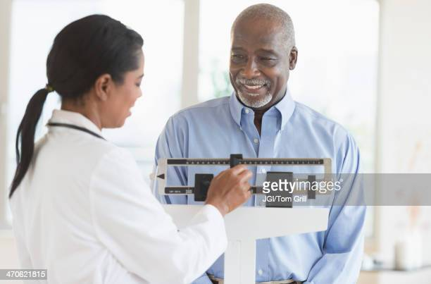 Black doctor weighing patient