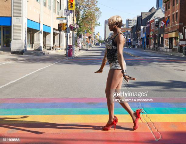Black drag queen walking on rainbow pavement on city street, Toronto, Ontario, Canada