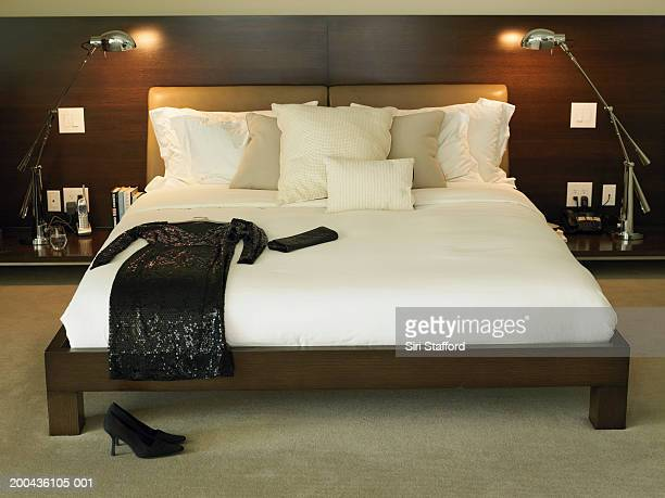 Black dress and purse on bed