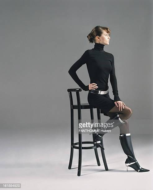 Black Dress Fashion Photo studio attitude JITKA profile sitting on a bar stool wearing a dress shirt black jersey collar brace Paco Rabanne black...