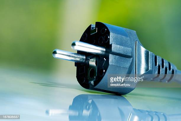 Black european houshold plug on green background