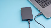 Black external hard disk connecting to a laptop on a blue background.