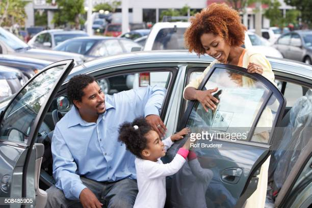 Black family admiring new car