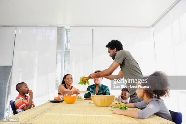 Black family eating salad at dining room table