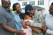 Black family greeting returning female soldier