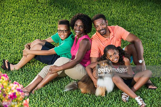 Black family of four sitting together on grass with dog