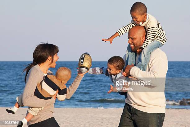 Black family playing football on beach