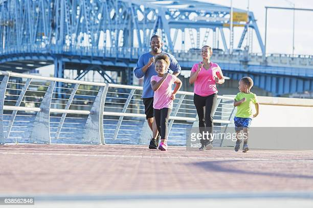 Black family staying fit, power walking on waterfront