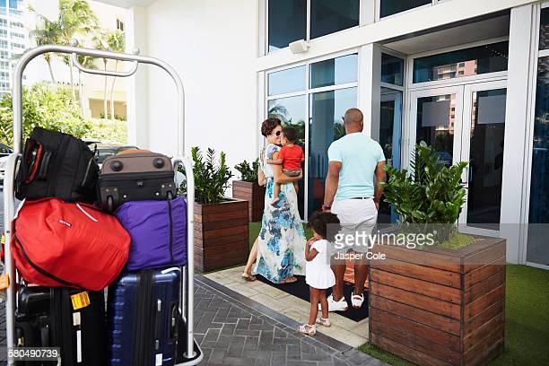 Black family walking into hotel lobby