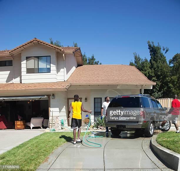 Black family washing car in driveway