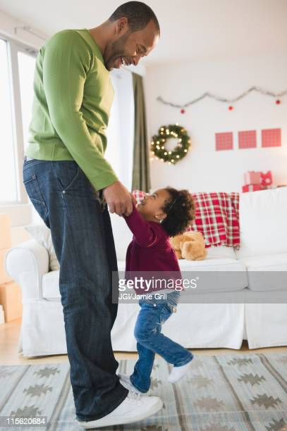 Black father and daughter dancing in living room