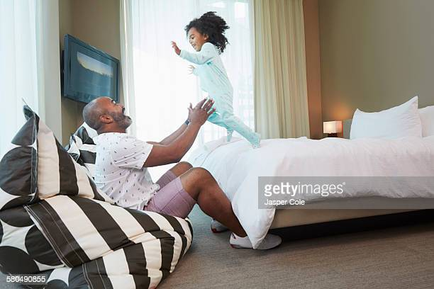 Black father and daughter playing in bedroom