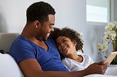 Black father and daughter relaxing in bed look at each other