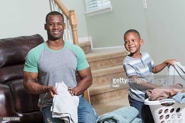 Black father and son doing laundry