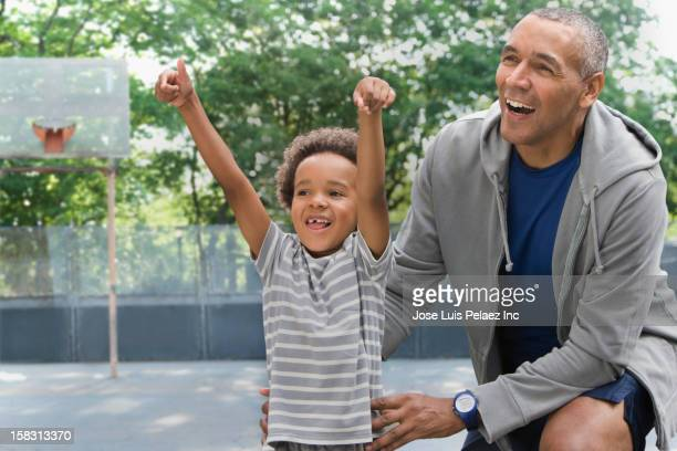 Black father and son on basketball court