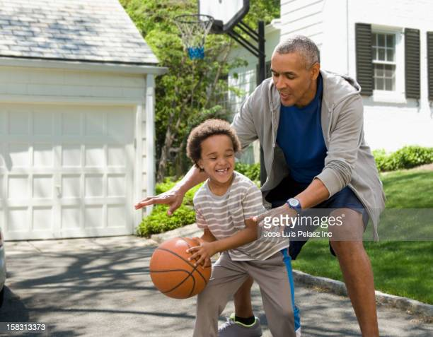 Black father and son playing basketball in driveway
