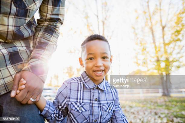 Black father and son walking in autumn leaves