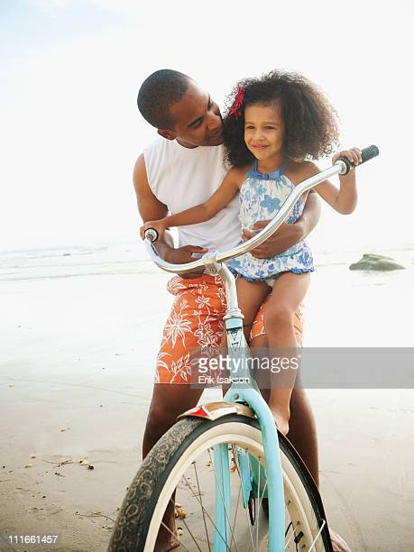 Black father helping daughter learn to ride retro bicycle