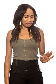 Black female isolated on a white background displaying disgust facial expressions.  She is young and of African American ethnicity.