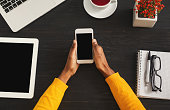 Black female hands holding smartphone with blank screen for advertisement. Top view of african-american hands, laptop keyboard, coffee, mobile on dark wooden table background, copy space