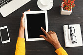 Black female hands on digital tablet with blank screen for advertisement. Top view of african-american hands, laptop keyboard, coffee, smartphone on a wooden office table background.