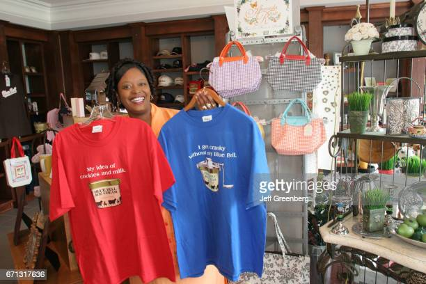 A Black female holding up shirts in the gift shop at Blue Bell Creameries