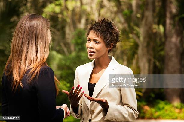 Black female office worker explaining herself to colleague outdoors