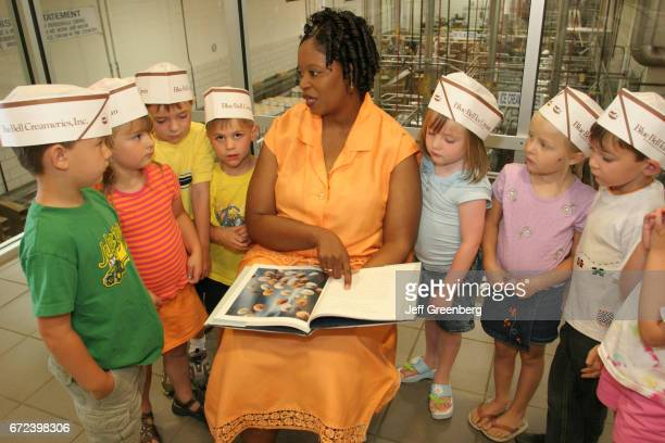 A Black female tour guide showing a book to a group of children at Blue Bell Creameries