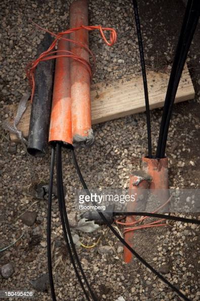 Black fiber optic internet cables sit on the ground during installation in Minneapolis Minnesota US on Thursday Aug 29 2013 The US Internet Corp...