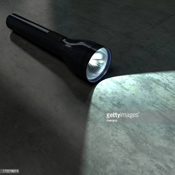 Black flashlight illuminating part of a dark metallic floor