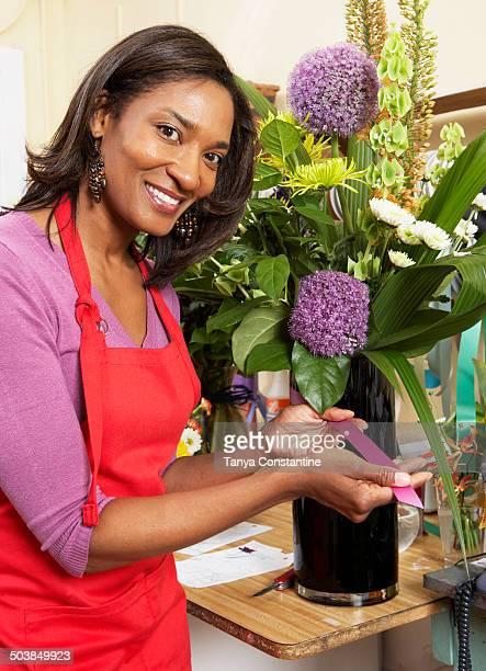 Black florist displaying flower arrangement